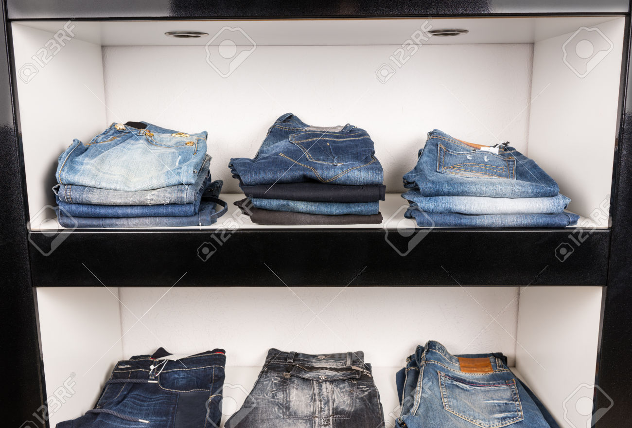 Jeans of Varying Color Washes and Styles Neatly Folded on Display Shelf in Clothing Boutique Store or Upscale Luxury Closet